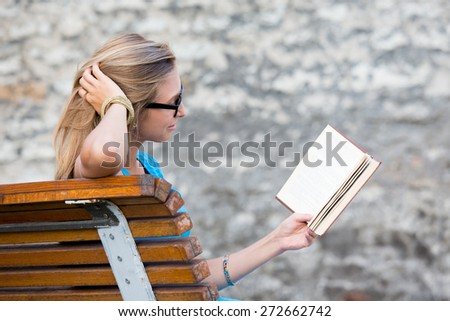 Young woman outdoors reading a book, side view.  - stock photo