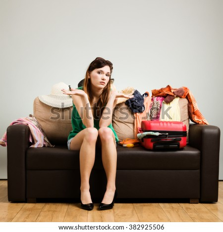 Young woman packing a travel bag on the plane before going on holiday. Gray background, easy to remove.