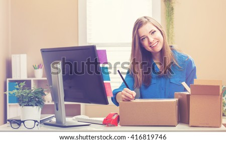 Young woman packing boxes to be shipped in her home office - stock photo
