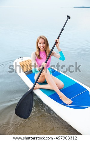 Young woman paddling on sup board with paddle. Sitting pose - concept of harmony with the nature, free and healthy living, freelance, remote business. - stock photo