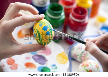 Young woman painting Easter eggs - stock photo