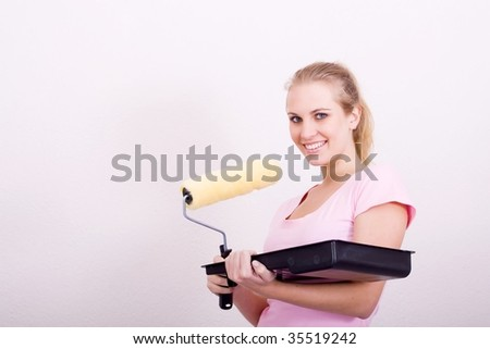 young woman painting her new home - stock photo