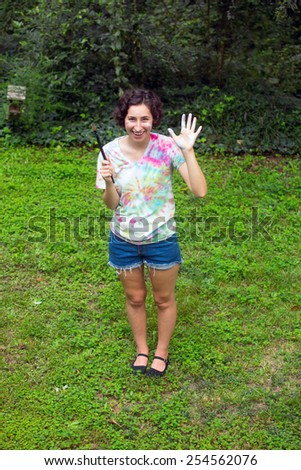 young  woman painting on canvas outside - stock photo
