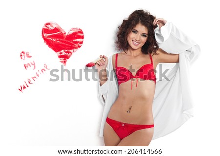 Young woman painting on the wall a red heart with paint brush in a be my valentine concept. Isolated on white. - stock photo