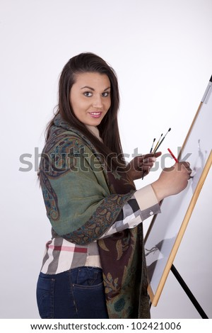 Young woman painting on white canvas.