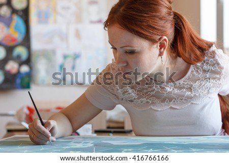 Young woman paints a picture in the studio .