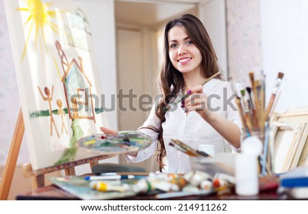Young woman paints home of dreams on canva - stock photo