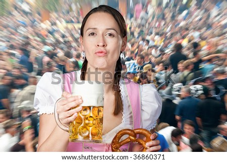 Young woman partying with a traditional mass of beer in Oktoberfest crowds - stock photo