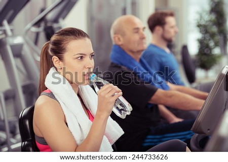 Young woman pausing during her workout to drink fresh bottled water in a gym with other people on equipment in the background - stock photo