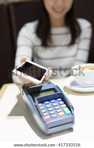 young woman pay by smart phone with empty screen in the restaurant, great for your design,asian beauty - stock photo
