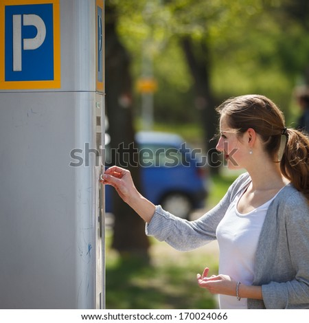 Young woman paying for parking - stock photo