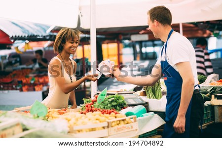 Young woman paying for produce at farmers market - stock photo