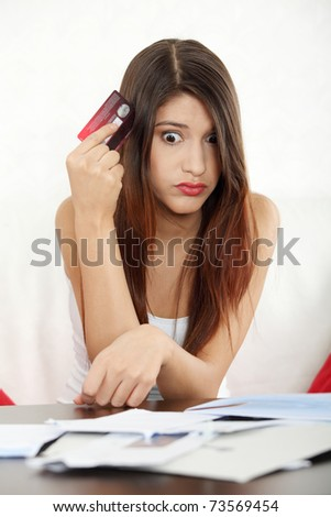 Young woman paying high bills online with credit card.