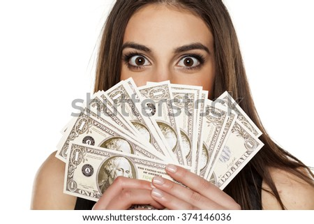 young woman peeking behind the stack of money in her hands