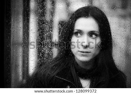 Young woman peeking behind waterdropped glass - stock photo