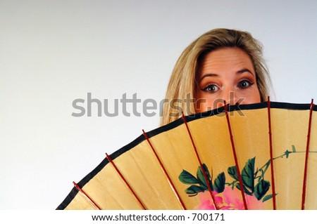 Young woman peeking over the top of a Japanese umbrella / parasol. - stock photo