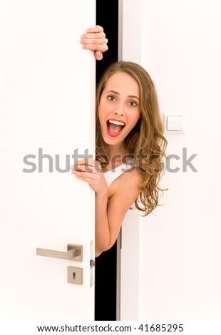 Young woman peeking through door - stock photo