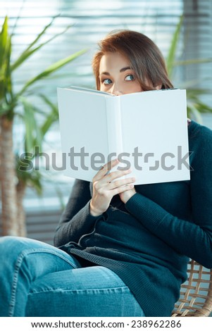 Young woman peeks from behind a book with a blank cover - stock photo