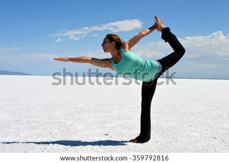 Young woman performing a yoga pose on the Bonneville Salt Flats in Utah. - stock photo