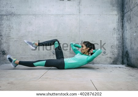 Young woman performing core crunch exercise - slight action blur in motion of activity = gritty urban outdoor location - stock photo