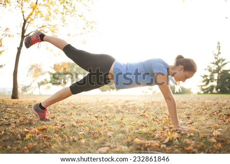Young woman performing yoga positions in park during autumn - stock photo