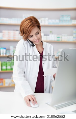 Young woman pharmacist talking on a phone as she stands behind her computer in the pharmacy checking information on a prescription she is holding - stock photo