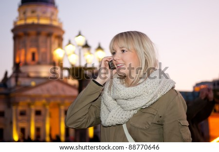 young woman phoned in the city at evening - stock photo