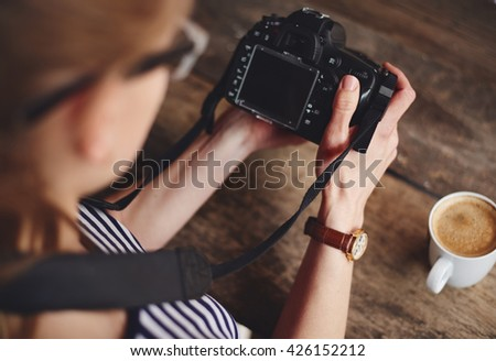 Young woman photographer looking at camera screen sitting at the table with cup of coffee. Concept of occupation and lifestyle.  - stock photo