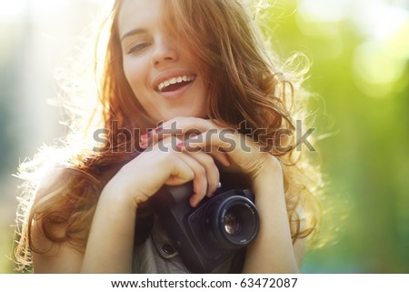 Young woman photographer. Soft colors, focus on mouth. - stock photo
