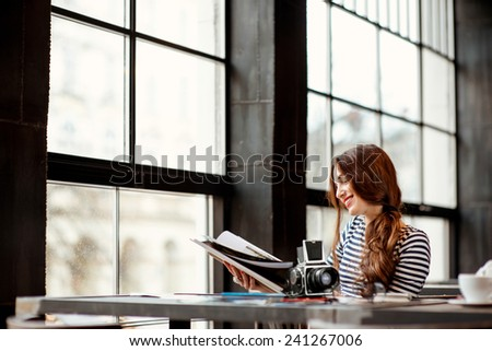 Young woman photographer watching photo album with old 6x6 frame camera and printed photos on the table sitting in the cafe with big windows - stock photo