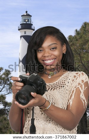 Young woman photographer with her dslr camera - stock photo