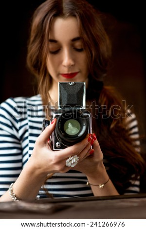 Young woman photographer with old 6x6 frame camera - stock photo