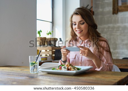 Young woman photographing her meal in restaurant - stock photo
