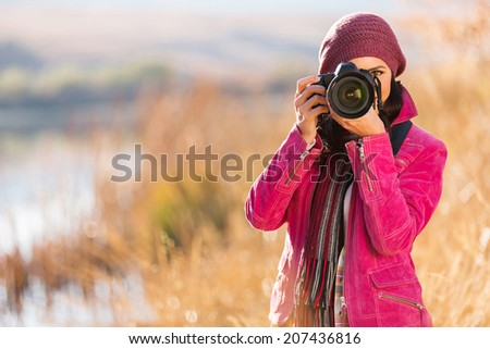 young woman photographing outdoors in autumn - stock photo