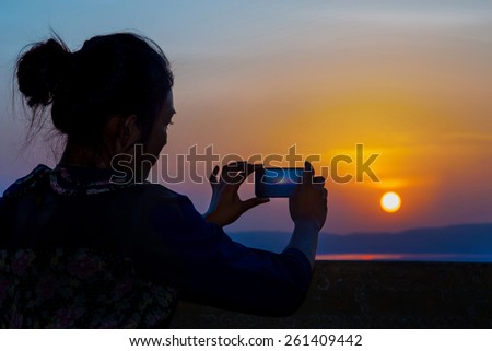 Young woman photographing sunset - stock photo