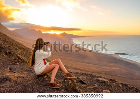 Young woman photographing with smart phone beautiful landscape with beach and mountains on the sunset on Fuerteventura island in Spain - stock photo