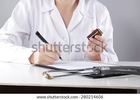 Young woman physician with stethoscope prescribing treatment to patient. Female doctor with pen writing recipe on clipboard in hospital. - stock photo