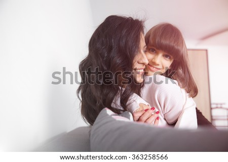 Young woman piggybacking her joyful little daughter at home in white lit room against the window. Smooth morning light, casual style - concept of happy family living and lifestyle