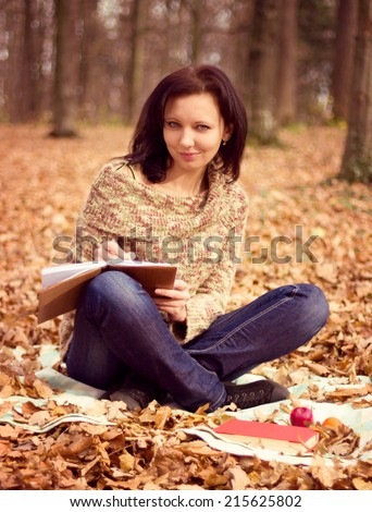Young woman planing, writing in the park - stock photo