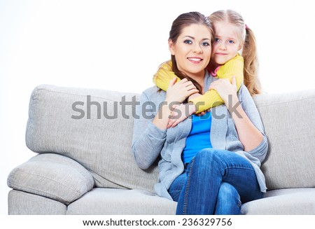 Young woman play with her daughter on sofa. Home portrait. - stock photo