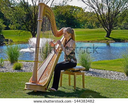 young woman playing a harp on a golf course - stock photo