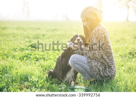 Young woman playing and enjoying the time with her dog - stock photo