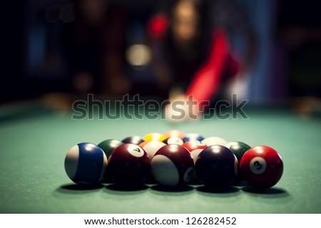 Young woman playing billiard - stock photo