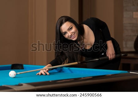Young Woman Playing Billiards Lined Up To Shoot Easy Winning Shot - stock photo