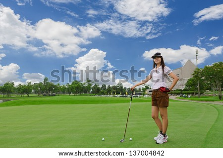 Young woman playing golf on a green golf course - stock photo