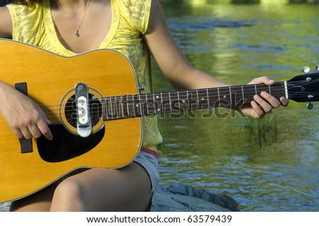 Young woman playing guitar by river in summer - stock photo