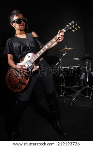 Young woman playing guitar during the concert