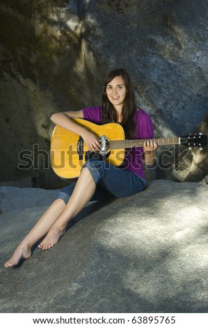 Young woman playing guitar on rocks in summer - stock photo