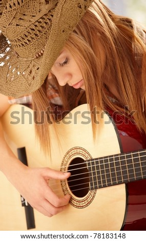 Young woman playing guitar with expression in western hat.? - stock photo