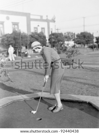 Young woman playing mini golf - stock photo